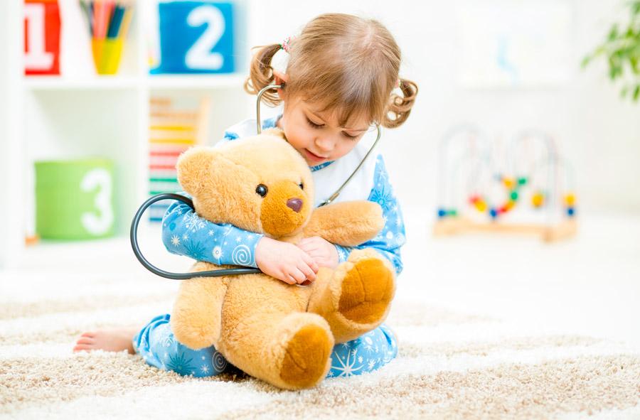 Niña pequeña con osito jugando a los médicos