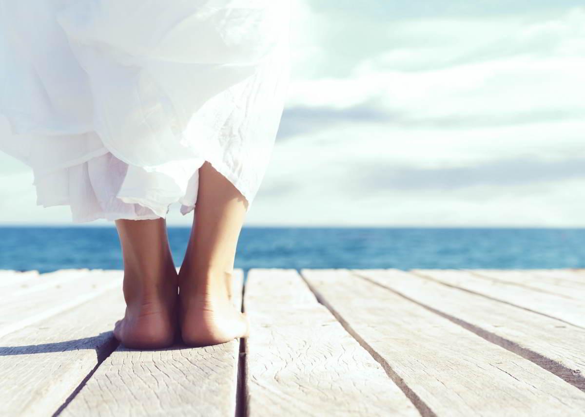 Imagen de unos pies cuidados frente al mar en verano